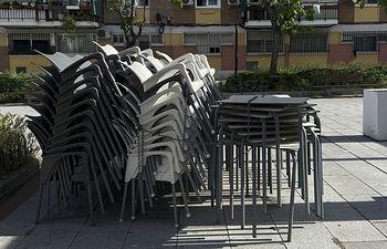 Sillas y mesas apiladas en una terraza cerrada. Foto: Europa Press 2020